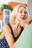Sad mature woman sitting on couch Stock Photo