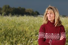 Sad mature woman standing in front of a flower field. Sad mature woman with crossed arms in front of a flower field stock image