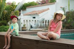 The melancholy, almost crying kids sitting near a pool apart from each other. The sad and melancholy, almost crying kids sitting near a pool apart from each royalty free stock image