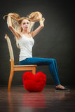 Sad melancholy woman with red heart pillow. Broken heart love concept. Sad melancholy woman sitting on chair red heart pillow on floor dark background Royalty Free Stock Image