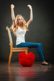 Sad melancholy woman with red heart pillow. Broken heart love concept. Sad melancholy woman sitting on chair red heart pillow on floor dark background Stock Photos