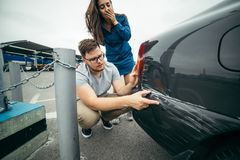 Sad man looking on car scratch, woman stand behind him. Sad men looking on car scratch, women stand behind him with sorrowful look Stock Photography