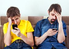 Sad Men with a Phones. Two Sad Men with a Phones on the Couch in the Room Stock Photos