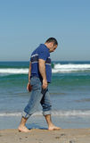 Sad men walking on the beach. Middle age caucasion men walking near the water on the beach with sadness Stock Images