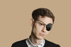 Sad mid adult man wearing eye patch over colored background Royalty Free Stock Photography