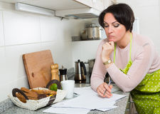 Sad middle aged housewife looking through bills Stock Image