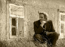 Sad middle-aged man sitting in front of an abandoned house. Vint Stock Photography