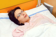 Sad middle-aged woman lying in hospital Stock Photography