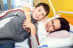 Sad middle-aged woman lying in hospital with son. Real people in real situation, sad middle-aged women lying in hospital with pneumonia, son visit his mother Royalty Free Stock Image