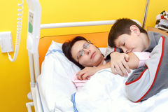 Sad middle-aged woman lying in hospital with son Stock Photo