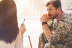 Sad military man wrinkling his forehead. Do not worry. Upset bearded soldier holding hands together and looking forward while sitting in semi position Royalty Free Stock Photo