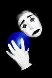 Sad mime. In dramatic makeup with blue balloon isolated on black background Stock Photo