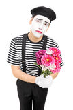 Sad mime artist holding a bouquet of flowers Stock Photos