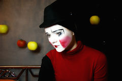 Sad mime in a hat with apples Stock Photo