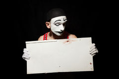 Sad mime holding white paper dirty sheet in hands Stock Image