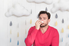 Sad miserable man wiping the nose with a paper tissue. Unpleasant illness. Unhappy depressed young man standing against the rainy background and wiping his nose Royalty Free Stock Photos