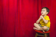 Sad Mixed Race Boy Sitting on Stool in Front of Curtain royalty free stock photography