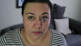 Sad mixed race woman. Sad mixed ethnicity woman looks up at camera with upset expression stock footage
