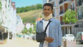 Sad mixed-race young man in foam cervical collar and arm sling sighing on camera
