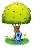 A sad monster under the cherry tree Royalty Free Stock Image