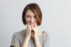Sad mood and pretense. Girl tries to pull a smile with fingers over her mouth Stock Image
