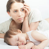 Sad mother with baby. Depressed woman, fatigue worries. Sleeping child. Headache Stock Photo