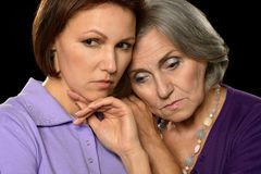Sad mother and daughter. On a black background Royalty Free Stock Images