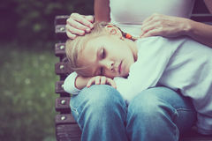 Sad mother and daughter sitting on bench in the park Royalty Free Stock Photo