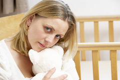 Sad Mother Sitting In Empty Nursery Royalty Free Stock Photography
