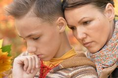 Close up portrait of sad mother and son in autumn park royalty free stock photography