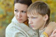 Sad mother with son in autumn park Stock Photos