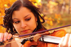 Sad Mountain Music. Woman playing a violin with a tear in her eye set in an autum color backdrop in the mountains Stock Image