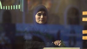 Sad Muslim lady in traditional hijab in cafe thinking about home, emigration. Stock photo stock images