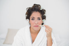 Sad natural brunette using thermometer Royalty Free Stock Photo