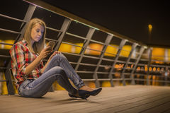 Sad news. Upset young woman with mobile phone reads the message Royalty Free Stock Images