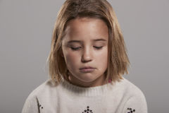 Sad nine year old girl looking down, head and shoulders Stock Images