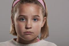Sad nine year old girl looking to camera, close up head shot Stock Photography