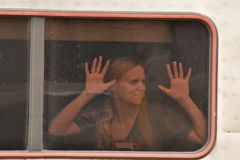 Woman in the train. Sad and nostalgic woman in a train looking outdoors, hands raised against train window , leaving the station royalty free stock photo