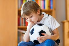 Sad and not happy little kid with football about lost football or soccer game. child after watching match on tv. Little blond preschool kid boy with ball royalty free stock photos