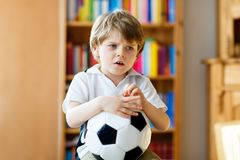 Sad and not happy little kid with football about lost football or soccer game. child after watching match on tv. Little blond preschool kid boy with ball Stock Photo