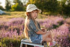 Sad offended child. Child girl in hat sitting on top stepladder outdoors royalty free stock images