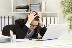 Sad office worker complaining after bankruptcy. Sitting in a desktop at workplace royalty free stock photo
