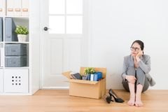 Sad office worker woman sitting on wood floor. Unemployment sad office worker women sitting on wood floor with company personal belongings box and daydreaming Royalty Free Stock Image
