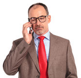 Sad old businessman talking on the phone Royalty Free Stock Images