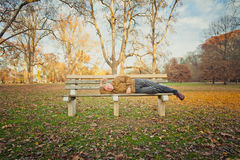 Sad Old Homeless Man. A sad old man outside sleeping on a bench. The image orientation is horizontal and there is copy space Stock Photography