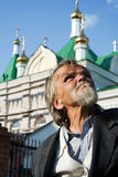 Sad old homeless man. Sad old man looking up against a cathedral Royalty Free Stock Image