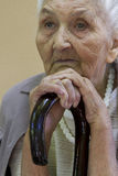 Sad old lady contemplating with walking stick Royalty Free Stock Images