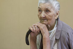 Sad old lady contemplating with walking stick Stock Photography