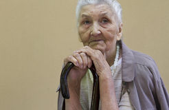 Sad old lady contemplating with walking stick Stock Photos