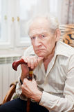Sad Old Man. Sad lonely old man sitting in an armchair with his cane stock photo